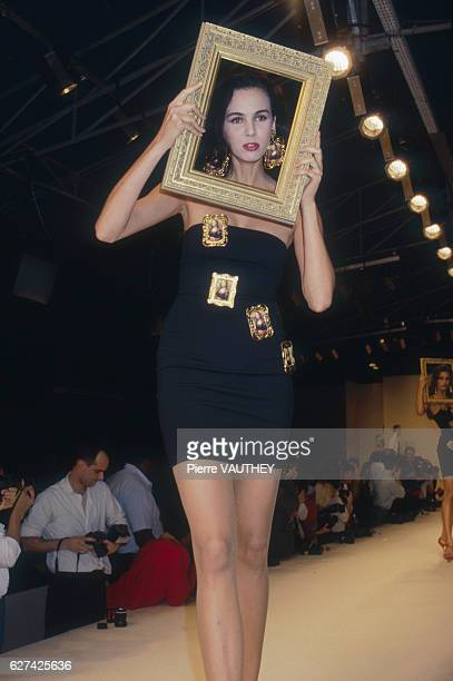 A fashion model wearing a black strapless readytowear cocktail dress by American fashion designer Patrick Kelly She holds a picture frame up to her...
