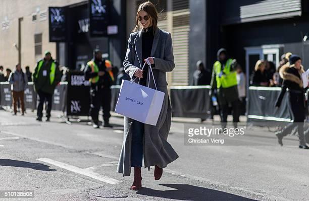 A fashion model wearing a long grey wool coat and a Derek Lam shopping bag seen outside Yigal Azrouel during New York Fashion Week Women's...