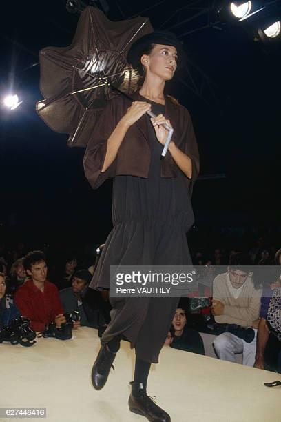 Fashion model wearing a ready-to-wear dress and short matching blazer with a brimmed hat and umbrella by Japanese fashion designer Yohji Yamamoto....