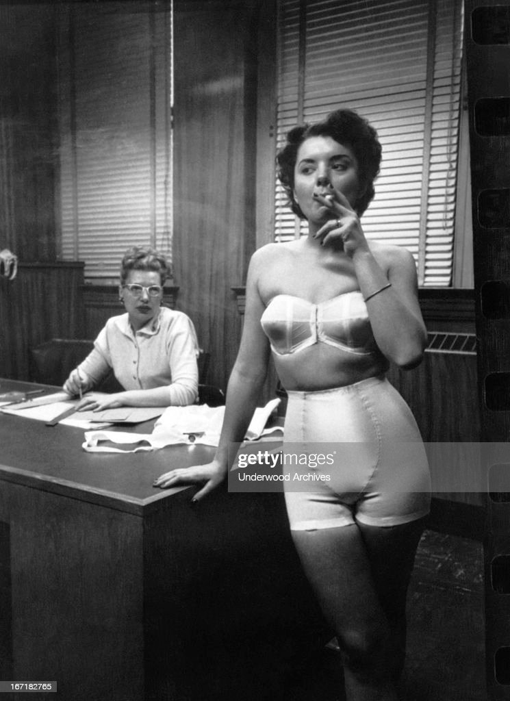 A fashion model wearing a strapless bra and girdle, standing in an office smoking, Chicago, Illinois, 1949.
