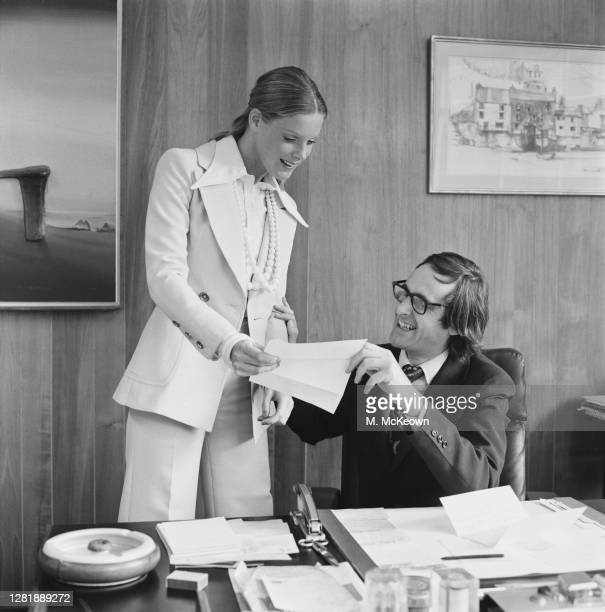 Fashion model wearing a trouser suit with a wide-collared crepe shirt hands a letter to a man behind a desk, who places his hand on her arm, 9th...