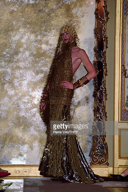 A fashion model wearing a women's haute couture black and gold colored evening dress and netting designed by French fashion designer JeanPaul...