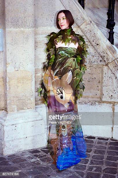 A fashion model wearing a women's haute couture evening dress with Bambi on it and a boa designed by French fashion designer JeanCharles de...