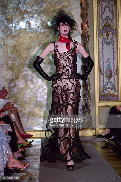 A fashion model wearing a women's haute couture evening dress with black curling ribbon black evening gloves and a red scarf designed by French...