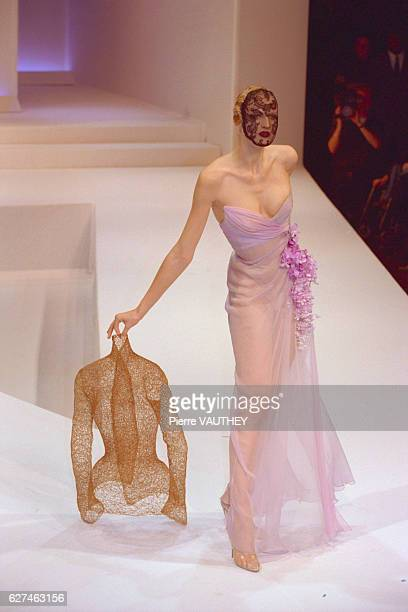 Fashion model wearing a women's haute couture light purple sheer evening gown, black face mask, and holding a gold colored jacket designed by German...