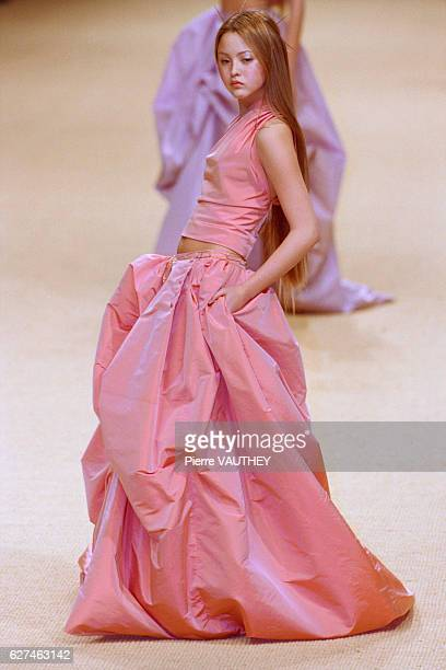 A fashion model wearing a women's haute couture pink halter and skirt designed by German fashion designer Karl Lagerfeld for French fashion house...