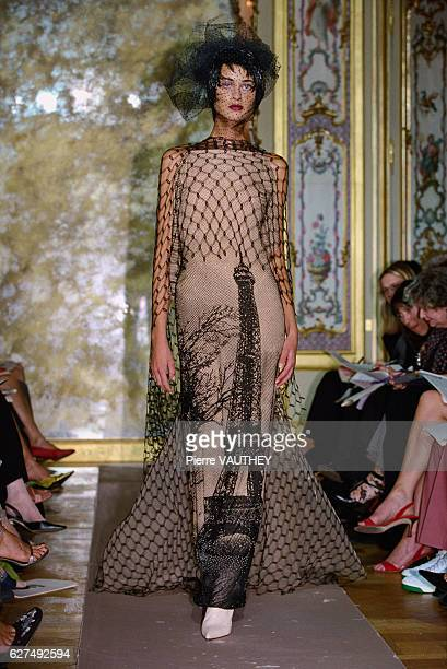 A fashion model wearing a women's haute couture tan and black evening dress with the Eiffel Tower on it designed by French fashion designer JeanPaul...