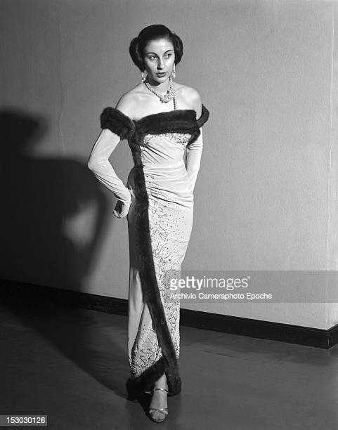 A fashion model wearing an edged with fur crepe evening dress from Veneziani fashion collection Cortina 16th January 1951