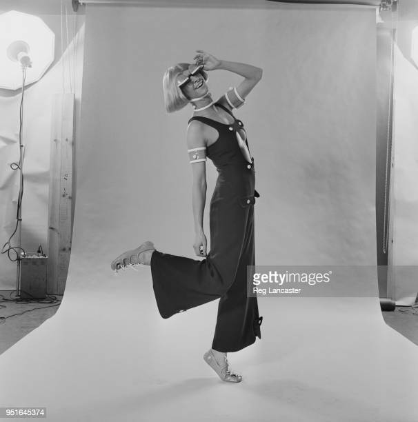 A fashion model wearing bosomrevealing cropped navy linen jumpsuit with white buttons pale blue armbands and choker and 'eyelid' blinders by French...