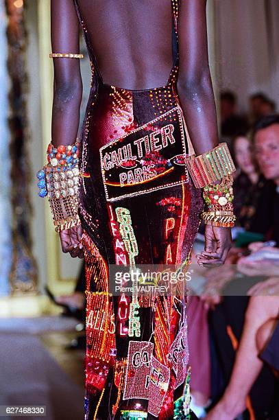 A fashion model wearing bracelets and a woman's haute couture multicolored evening dress with Gaultier Paris on it designed by French fashion...