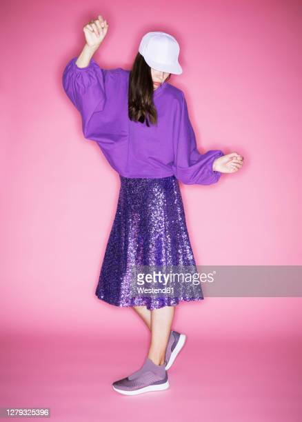fashion model wearing cap posing against pink background - purple dress stock pictures, royalty-free photos & images