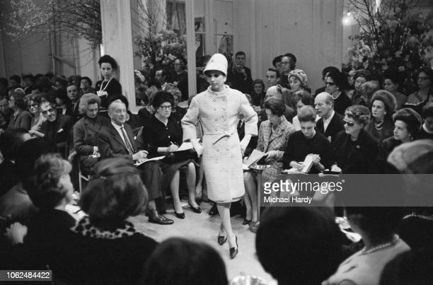 Fashion model wearing double-breasted midi coat and cloche hat walking the catwalk at a Yves Saint Laurent fashion show, UK, 4th February 1963.
