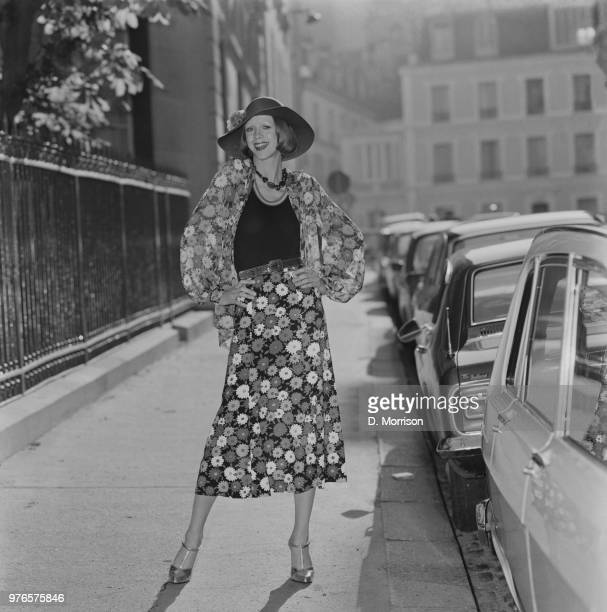 A fashion model wearing floral pattern shirt and midi skirt with bodysuit and hat by Yves Saint Laurent London UK 25th October 1973