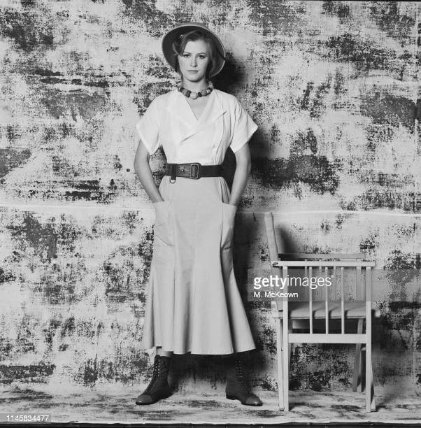 A fashion model wearing safari ranger inspired outfit including v neck shirt long skirt with pockets belt necklace with large pearls and safari...