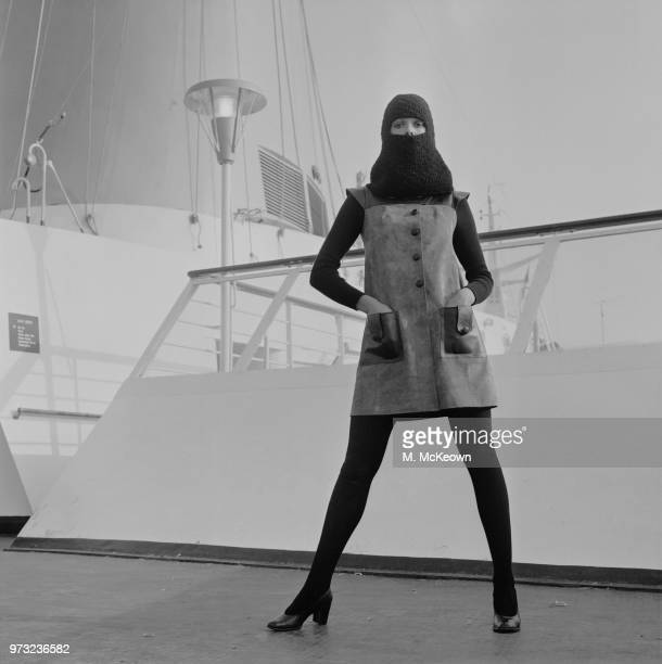 Fashion model wearing suede dress with leather pockets, black long-sleeved shirt, black stockings and balaclava, aboard a passenger ship, UK, 3rd...
