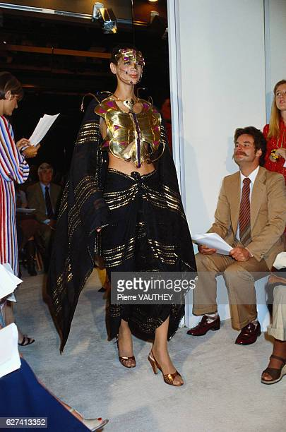 A fashion model wears a black haute couture skirt and gold breastplate by French fashion designer Emanuel Ungaro She modeled the outfit during his...