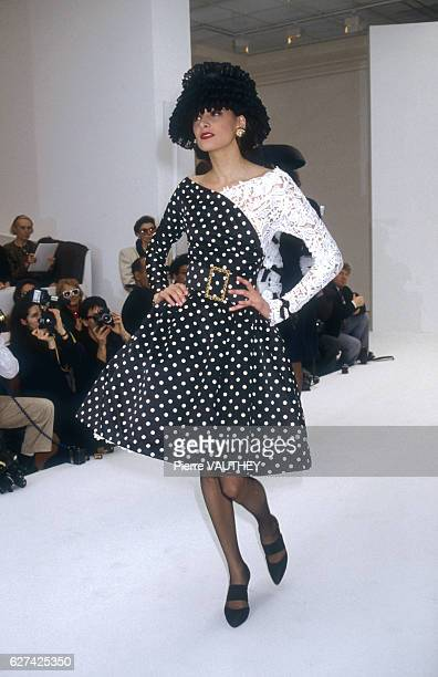 A fashion model wears a blackandwhite polk dot haute couture cocktail dress by German fashion designer Karl Lagerfeld for French fashion house Chanel...