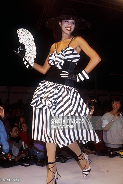 A fashion model wears a blackandwhite striped readytowear cocktail dress and brimmed hat by German fashion designer Karl Lagerfeld for French fashion...
