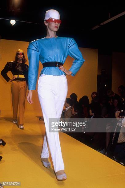 A fashion model wears a bright blue haute couture shirt with shoulder pads and white slacks by French fashion designer Pierre Cardin She modeled the...
