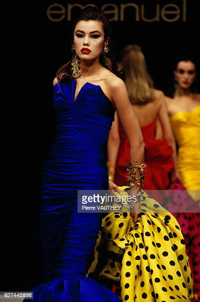 A fashion model wears a brightly colored haute couture evening gown with a polka dot wrap by French fashion designer Emanuel Ungaro during his...