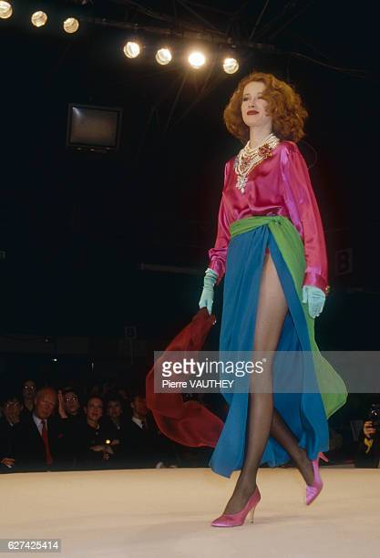 A fashion model wears a brightly colored readytowear cocktail dress and sash by French fashion designer Yves Saint Laurent She modeled the dress...