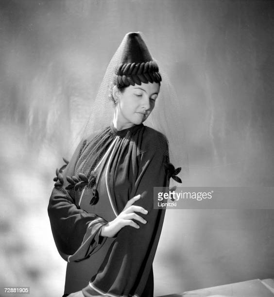 A fashion model wears a conical felt hat with a veil designed by French fashion designer Jeanne Lanvin Paris September 1937