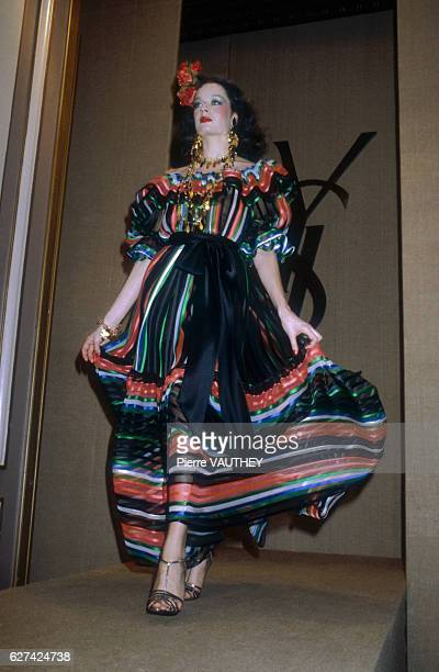 A fashion model wears a flamencostyle striped haute couture evening gown by French fashion designer Yves Saint Laurent She modeled the gown during...