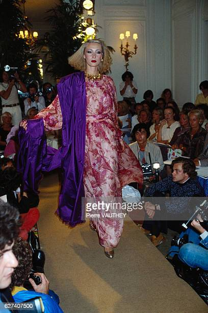 A fashion model wears a floral print haute couture dress with a purple wrap by French fashion designer Marc Bohan for the Christian Dior fashion...