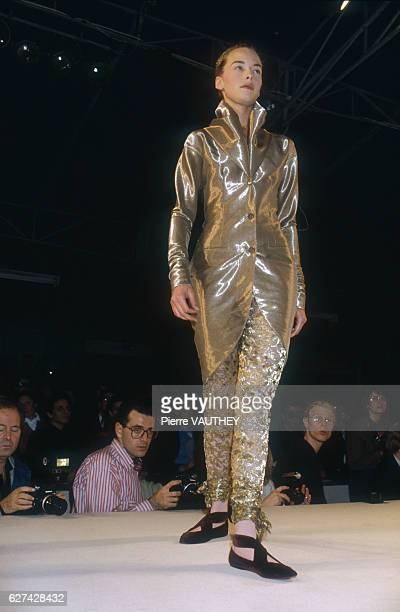 A fashion model wears a gold readytowear shirt and pants outfit by Italian fashion designer Romeo Gigli She models the outfit during his AutumnWinter...