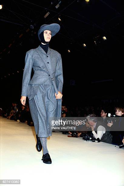 Fashion model wears a gray blazer and short pants with a hat by Japanese fashion designer Yohji Yamamoto at his autumn-winter 1986-1987 fashion show...