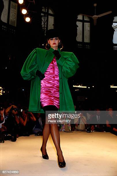 A fashion model wears a green coat over a magenta cocktail dress by French fashion designer Emanuel Ungaro at his autumnwinter 19861987 fashion show...