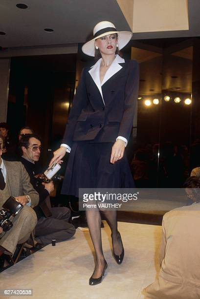 A fashion model wears a haute couture blazer and skirt with a brimmed hat by French fashion designer Hubert de Givenchy She modeled the suit during...
