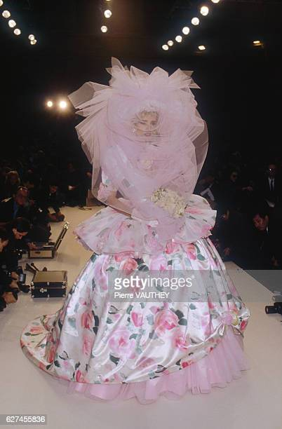 A fashion model wears a haute couture floral print evening gown and large veiled headdress by French fashion designer Emanuel Ungaro She modeled the...