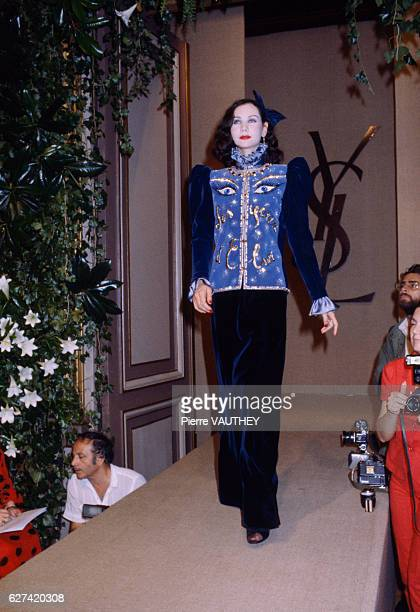 A fashion model wears a haute couture highcollar jacket with matching navy blue slacks by French fashion designer Yves Saint Laurent She modeled the...