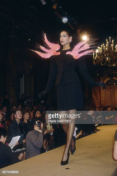 Fashion model wears a haute couture suit with pink accents by French fashion designer Yves Saint Laurent. She is modeling the suit during his...