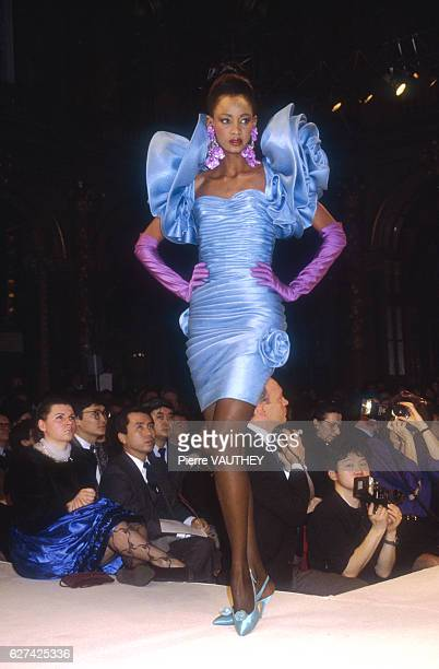A fashion model wears a light blue ruffled haute couture cocktail dress by French fashion designer Emanuel Ungaro She is modeling the dress during...
