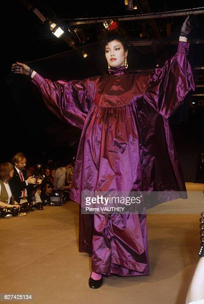 Fashion model wears a long, purple haute couture dress by Japanese fashion designer Kenzo Takada. She modeled the dress during his Autumn-Winter...