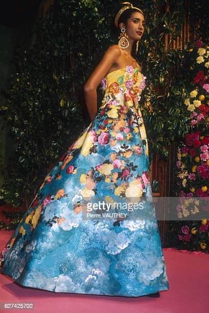 A fashion model wears a long strapless haute couture evening gown with floral patterns by French fashion designer Christian Lacroix She modeled the...