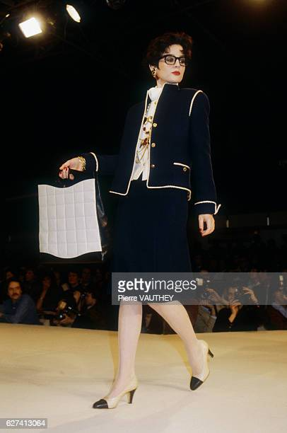 A fashion model wears a navy blue haute couture suit and purse by German fashion designer Karl Lagerfeld for French fashion house Chanel She modeled...