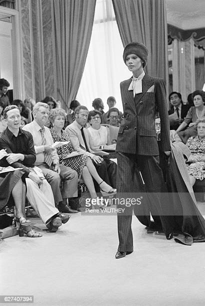 A fashion model wears a pantsuit and fur hat by French fashion designer Yves Saint Laurent during his 19751976 FallWinter haute couture fashion show...