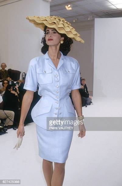 A fashion model wears a pastel haute couture suit by German fashion designer Karl Lagerfeld for French fashion house Chanel She is modeling the suit...
