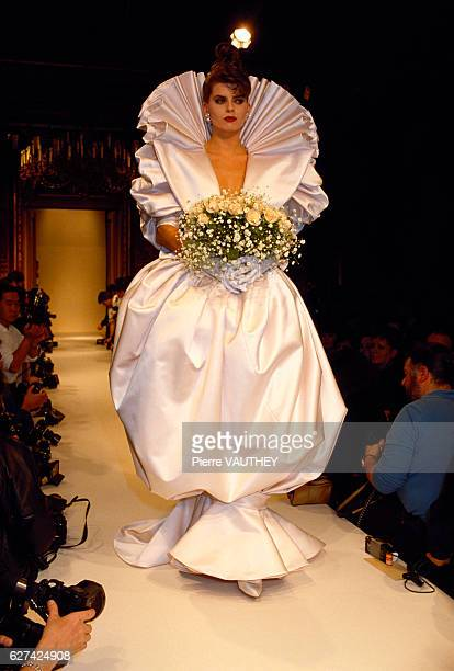 A fashion model wears a puffy white wedding dress with a large pleated collar by French fashion designer Emanuel Ungaro at his springsummer 1987...