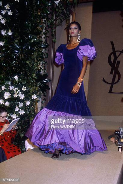 Fashion model wears a purple velvet haute couture evening gown with ruffles and puffed sleeves by French fashion designer Yves Saint Laurent. She...