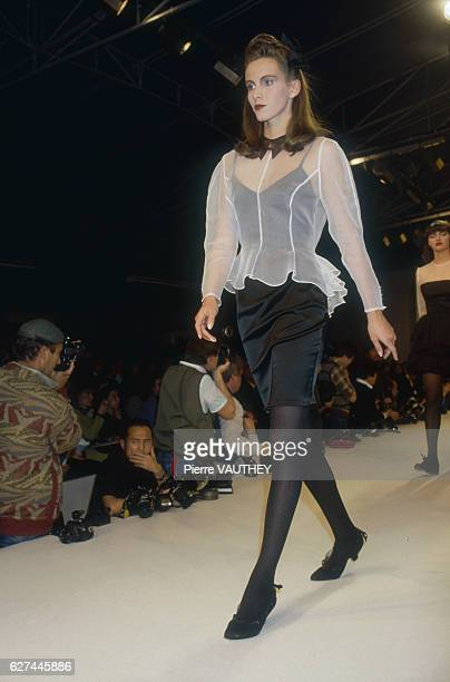 A fashion model wears a readytowear cocktail dress and sheer jacket by French fashion designer Lolita Lempicka She is modeling the dress during the...