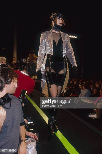 A fashion model wears a readytowear corset outfit with a silver jacket by French fashion designer Jean Paul Gaultier She models the outfit during his...