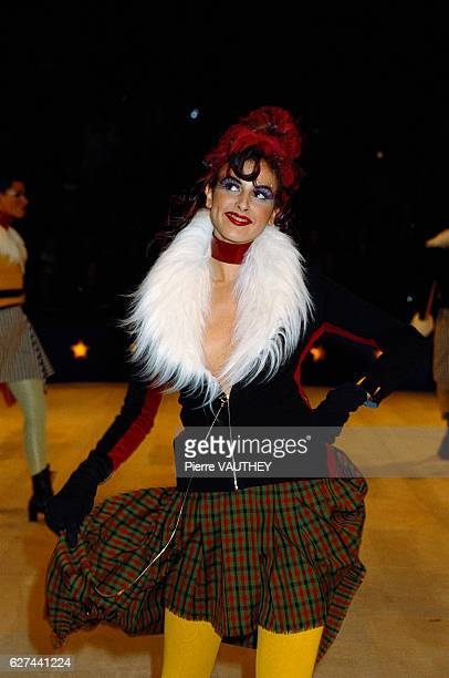A fashion model wears a readytowear jacket with a white faux fur collar and plaid skirt by French fashion designer Jean Paul Gaultier She modeled the...