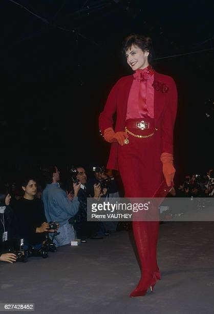 A fashion model wears a readytowear red suit with matching gloves and purse by German fashion designer Karl Lagerfeld for French fashion house Chanel...
