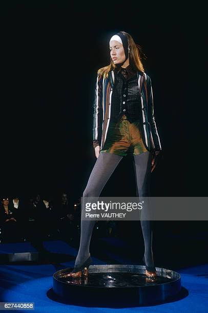 A fashion model wears a readytowear striped blazer with a shirt and hot pants by French fashion designer Jean Paul Gaultier She modeled the outfit...