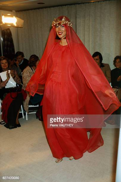 A fashion model wears a red haute couture evening gown with a matching veil by French fashion designer JulesFrancois Crahay for the Lanvin fashion...