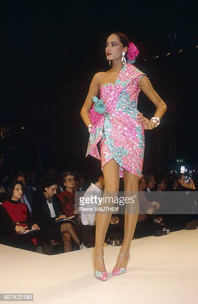 A fashion model wears a short pink and green haute couture cocktail dress by French fashion designer Hubert de Givenchy She is modeling the dress...